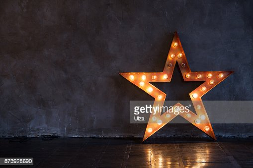 Decorative star with lamps on a background of wall. Modern grungy interior : Stock Photo