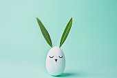 Decorative White Painted Easter Egg Bunny with Drawn Cute Kawaii Face. Green Leaves as Ears. Pastel Turquoise Background. Spring Holiday Crafts Kids Concept. Greeting Card Poster Banner