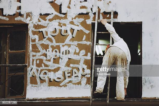A decorator applies filler to cracks on a wall in Paris France circa 1960