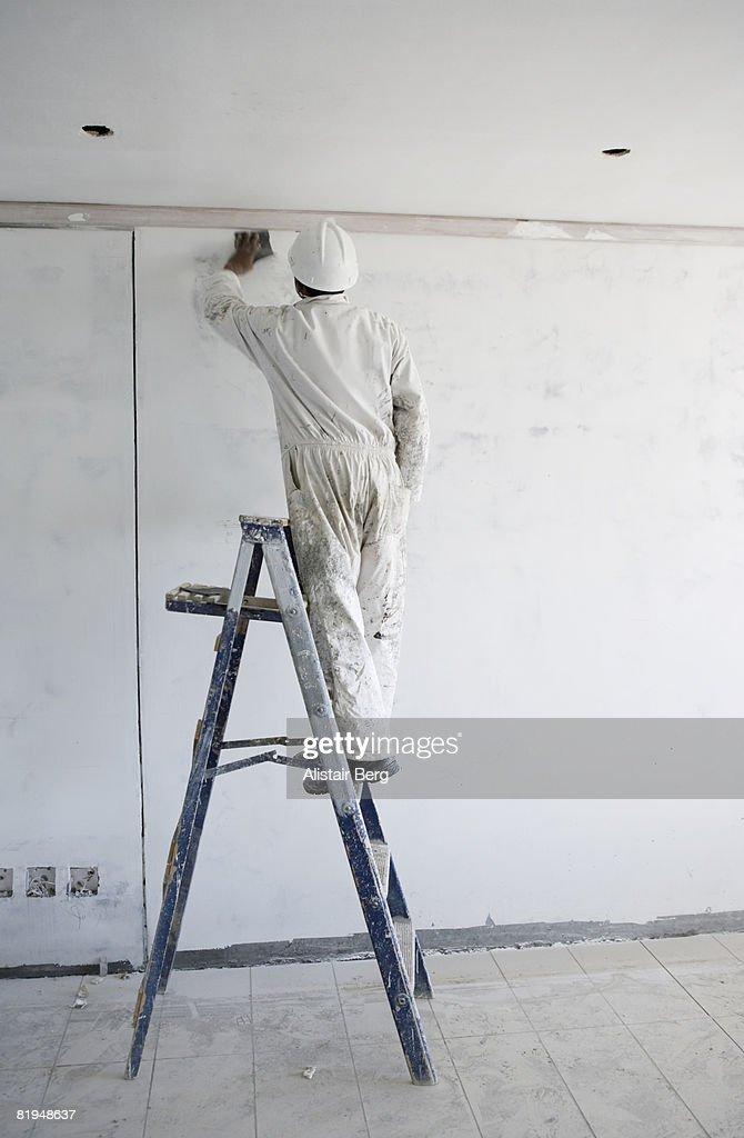 Decorator sanding down wall  : Stock Photo