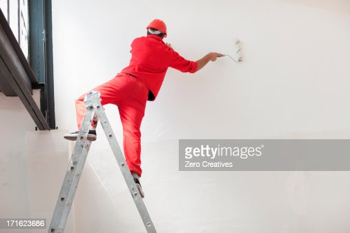 Decorator straddling step ladder