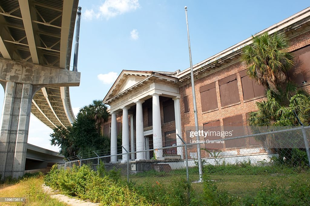 CONTENT] Decrepit public school with Doric columns and boarded windows visible from I-95 in downtown Jacksonville, Florida. The original wooden Riverside Park School was built in 1891. More than twenty years and multiple additions later, Duval County declared it a fire hazard. Public School Number Four was one of several brick school houses built to accomodate the city's growing community. Construction ensued from 1917 to 1918 and cost over $250,000. The school was eventually renamed Annie Lytle Elementary School in honor of a long-time teacher and principal. In the 1950s, the erection of I-95 and I-10 separated it from Riverside Park. Removed from the public, the school ceased operations in 1960. After serving as storage and office space, the former Public School Number Four was condemned in 1971. Since then, it has succumbed to at least one fire, collapse, the homeless, adventurous youth, gangs, paranormal activity, historic landmark designation, and on-again off-again plans for demolition.