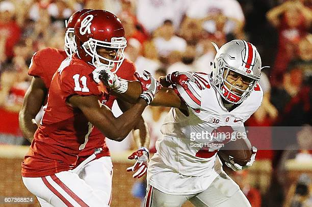 Dede Westbrook of the Oklahoma Sooners tackles Marshon Lattimore of the Ohio State Buckeyes as he ran an interception back in the first half of their...
