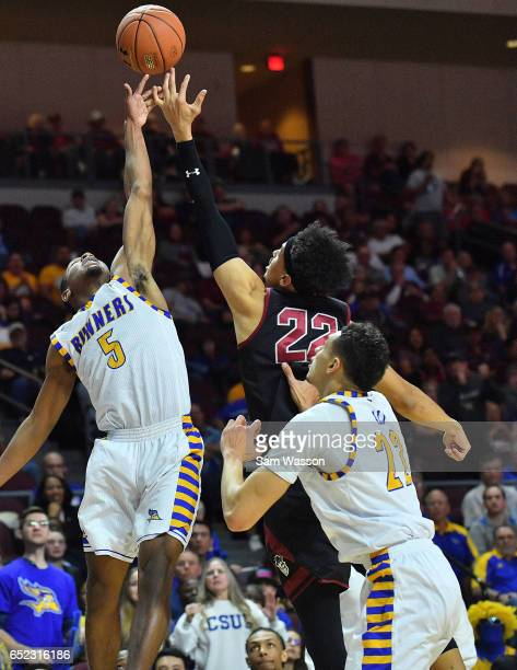 Dedrick Basile of the Cal State Bakersfield Roadrunners and Eli Chuha of the New Mexico State Aggies battle for a rebound as Moataz Aly of the Cal...
