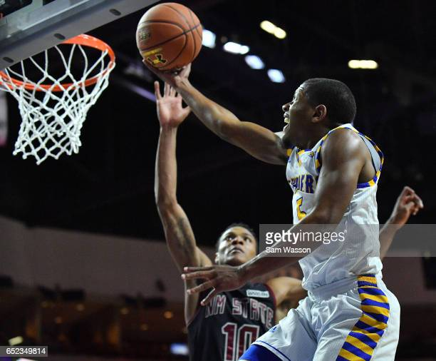 Dedrick Basile of the Cal State Bakersfield Roadrunners goes up for a layup against Jemerrio Jones of the New Mexico State Aggies during the...