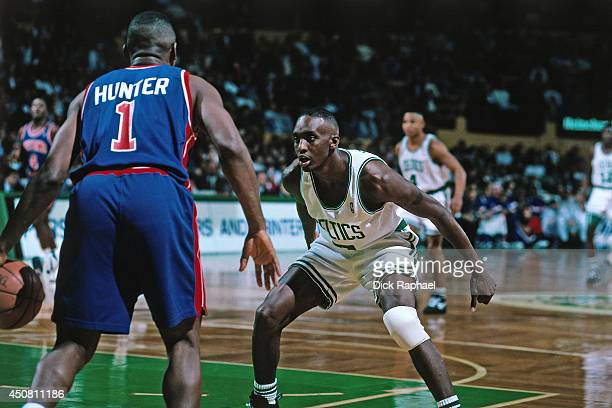 Dee Brown of the Boston Celtics guards his position against Lindsey Hunter of the Detroit Pistons during a game played in 1995 at the Boston Garden...