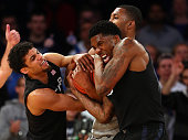 Dee Davis and Jalen Reynolds of the Xavier Musketeers battle with Mikael Hopkins of the Georgetown Hoyas for a loose ball during a semifinal game of...