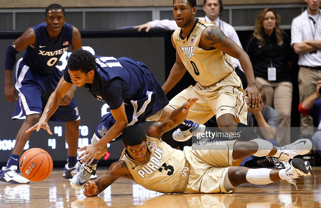 Dee Davis #11 of the Xavier Musketeers and Ronnie Johnson #3 of the Purdue Boilermakers scramble for a loose ball at Mackey Arena on December 1, 2012 in West Lafayette, Indiana.