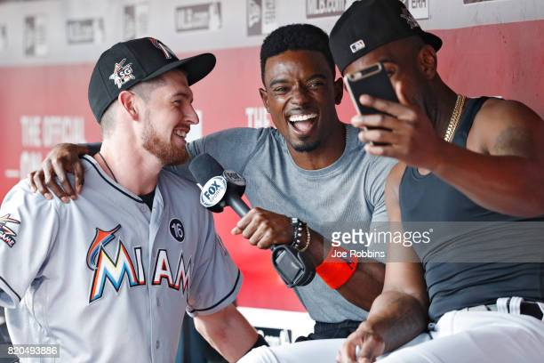 Dee Gordon and JT Riddle of the Miami Marlins conduct an interview in the dugout while waiting out a rain delay before the start of a game against...