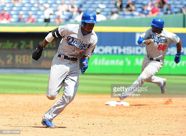 Dee Gordon and Yasiel Puig of the Los Angeles Dodgers round second base during the ninth inning against the Atlanta Braves at Turner Field on August...