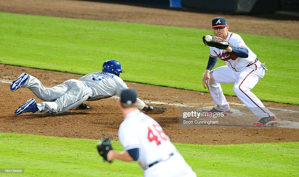 <a gi-track='captionPersonalityLinkClicked' href=/galleries/search?phrase=Dee+Gordon&family=editorial&specificpeople=7091343 ng-click='$event.stopPropagation()'>Dee Gordon</a> #9 of the Los Angeles Dodgers dives back to first base as <a gi-track='captionPersonalityLinkClicked' href=/galleries/search?phrase=Craig+Kimbrel&family=editorial&specificpeople=6795784 ng-click='$event.stopPropagation()'>Craig Kimbrel</a> #46 throws to <a gi-track='captionPersonalityLinkClicked' href=/galleries/search?phrase=Freddie+Freeman&family=editorial&specificpeople=5743987 ng-click='$event.stopPropagation()'>Freddie Freeman</a> #5 of the Atlanta Braves in the ninth inning during Game Two of the National League Division Series at Turner Field on October 4, 2013 in Atlanta, Georgia.