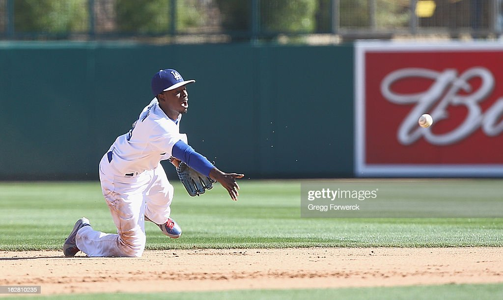 Dee Gordon of the Los Angeles Dodgers gloves a ball up the middle and starts a double play during a spring training baseball game against the San Francisco Giants at Camelback Ranch on February 26, 2013 in Glendale, Arizona.