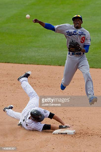 Dee Gordon of the Los Angeles Dodgers makes an acrobatic throw to first base while jumping over a sliding Michael Cuddyer of the Colorado Rockies...