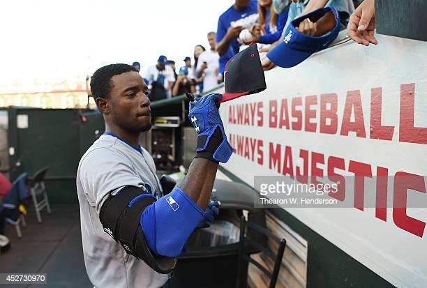 Dee Gordon of the Los Angeles Dodgers signs autographs for fans prior to the start of the game against the San Francisco Giants at ATT Park on July...
