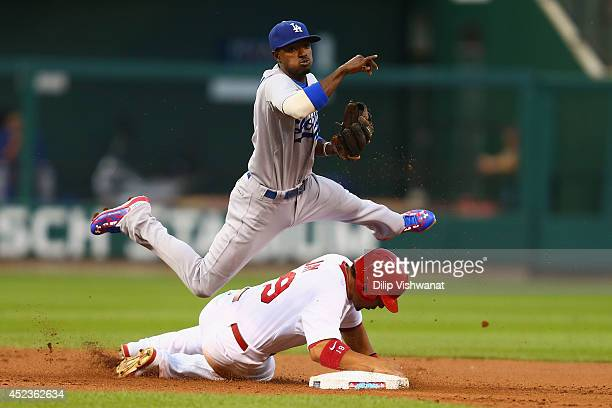 Dee Gordon of the Los Angeles Dodgers turns a double play over Jon Jay of the St Louis Cardinals in the second inning at Busch Stadium on July 18...
