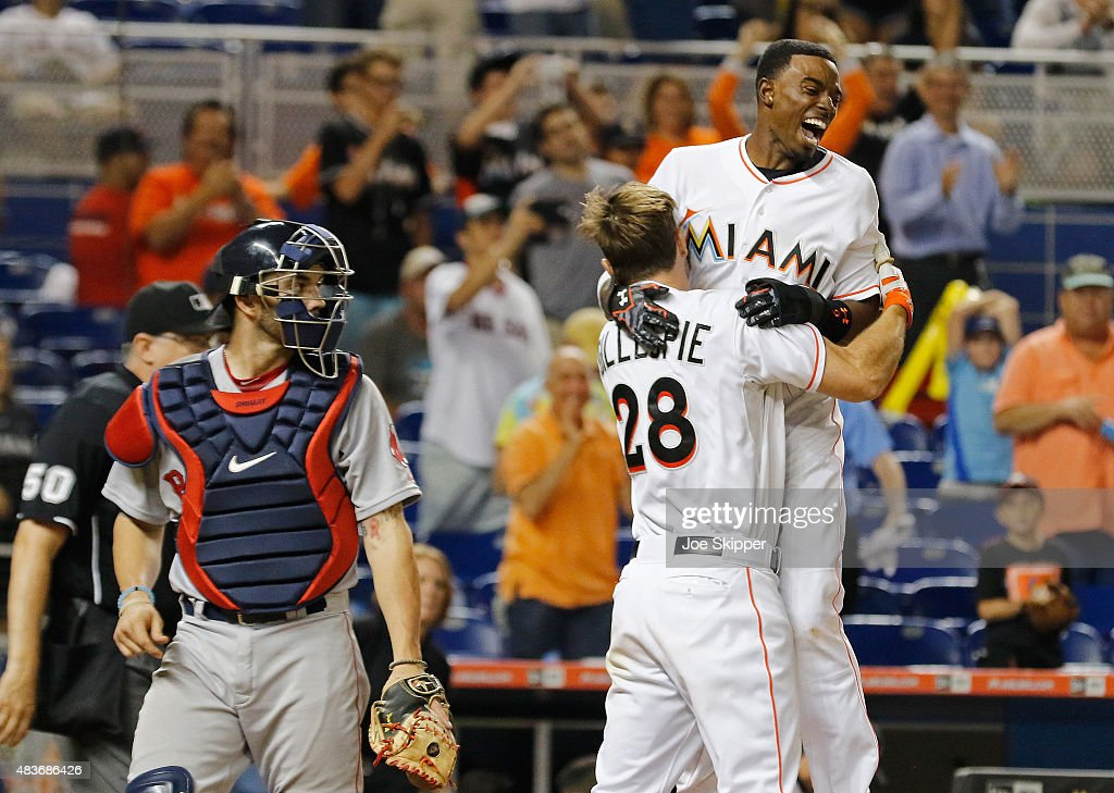 Dee Gordon #9 of the Miami Marlins celebrates his game-winning score with teammate Cole Gillespie #28 of the Miami Marlins at home plate with Blake Swihart #23 of the Boston Red Sox at left at Marlins Park on August 11, 2015 in Miami, Florida. The Marlins won the game in the 10th inning, 5-4.