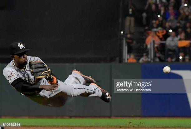 Dee Gordon of the Miami Marlins dives and throws to first base throwing out Brandon Crawford of the San Francisco Giants on the play in the bottom of...