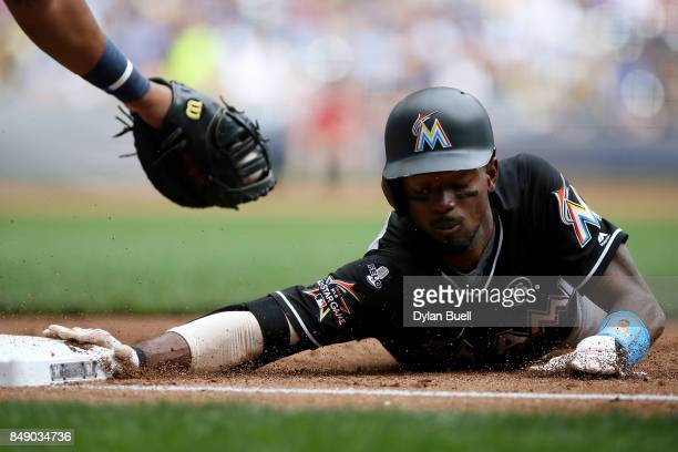 Dee Gordon of the Miami Marlins dives back into first base past the tag attempt by Jesus Aguilar of the Milwaukee Brewers during a pickoff attempt in...