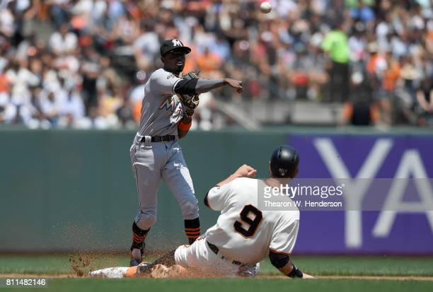 Dee Gordon of the Miami Marlins gets his throw off completing the doubleplay over the top of Brandon Belt of the San Francisco Giants in the bottom...