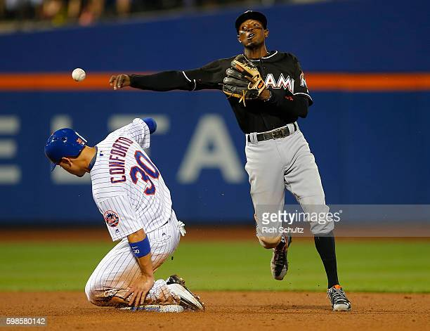 Dee Gordon of the Miami Marlins gets the force out on Michael Conforto of the New York Mets and throws to first base to get James Loney for a double...