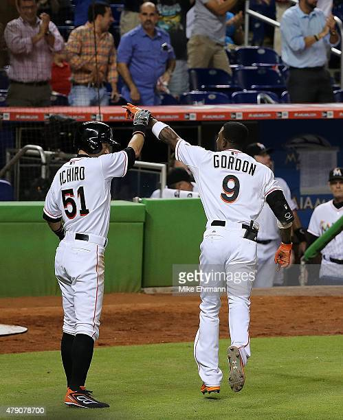 Dee Gordon of the Miami Marlins is congratulated by Ichiro Suzuki after he scores a 3RBI inside the park home run during a game against the San...