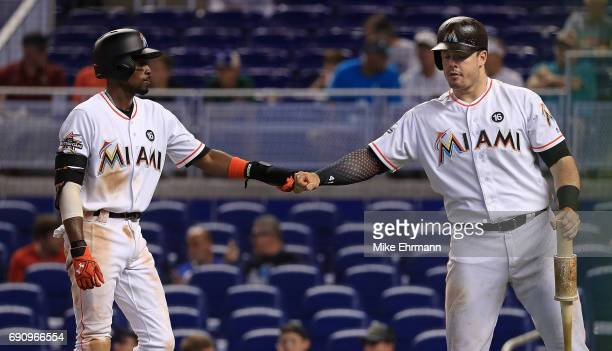 Dee Gordon of the Miami Marlins is congratulated by Justin Bour after scoring a run in the first inning during a game against the Philadelphia...