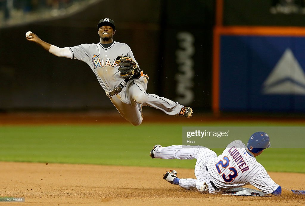 Dee Gordon #9 of the Miami Marlins is unable to turn the double play as Michael Cuddyer #23 of the New York Mets is out at second base on April 18, 2015 at Citi Field in the Flushing neighborhood of the Queens borough of New York City.Eric Campbell of the New York Mets was safe at first.