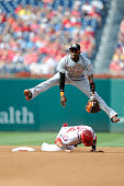 Dee Gordon of the Miami Marlins jumps over Ian Desmond of the Washington Nationals after completing a double play in the fourth inning at Nationals...