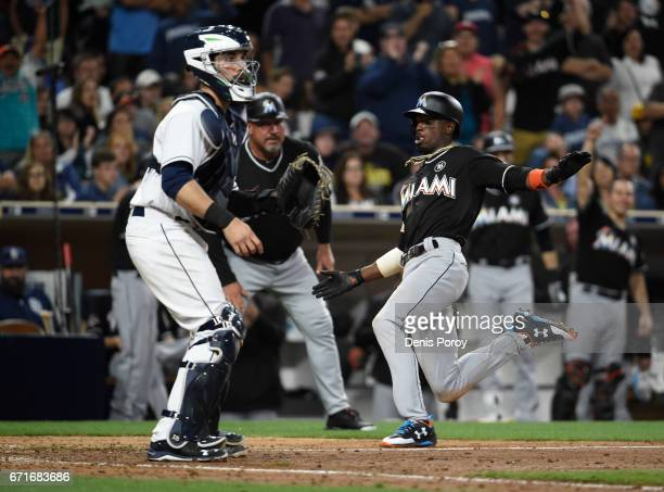 Dee Gordon of the Miami Marlins scores ahead of the throw to Austin Hedges of the San Diego Padres during the eleventh inning of a baseball game at...