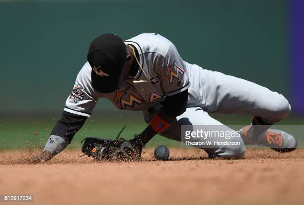 Dee Gordon of the Miami Marlins slides down to a knee to field a ground ball off the bat of Brandon Crawford of the San Francisco Giants in the...