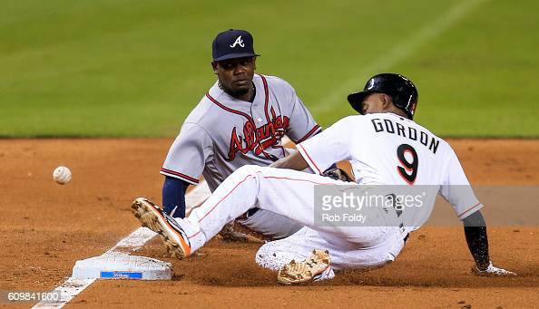 Dee Gordon of the Miami Marlins slides into third base for a triple as the ball gets past Adonis Garcia of the Atlanta Braves during the third inning...