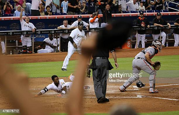 Dee Gordon of the Miami Marlins slides past Andrew Susac of the San Francisco Giants as he scores a 3RBI inside the park home run during a game at...