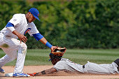 Dee Gordon of the Miami Marlins steals second base as Addison Russell of the Chicago Cubs takes the throw during the eighth inning at Wrigley Field...