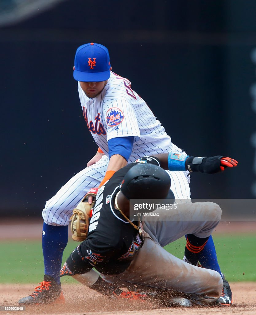 Dee Gordon #9 of the Miami Marlins steals second base in the third inning ahead of the tag from Gavin Cecchini #2 of the New York Mets at Citi Field on August 20, 2017 in the Flushing neighborhood of the Queens borough of New York City.