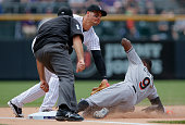 Dee Gordon of the Miami Marlins tries to stretch out a triple and is tagged out by third baseman Nolan Arenado of the Colorado Rockies in the first...