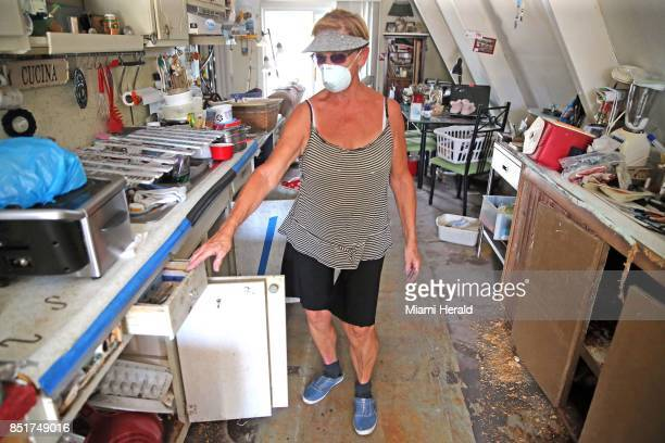 Dee Thorne walks through her home on Big Pine Key in the Florida Keys damaged during Hurricane Irma on September 20 2017 She wears a mask to protect...