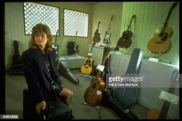 Dee Twitty wife of the late c/w singer Conway Twitty sitting amid Conway's vintage guitars at auction to settle family feud over his estate