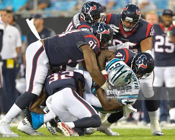 Dee Virgin Carlos Watkins and Zach Cunningham of the Houston Texans tackle Chris Manhertz of the Carolina Panthers during the preseason game at Bank...