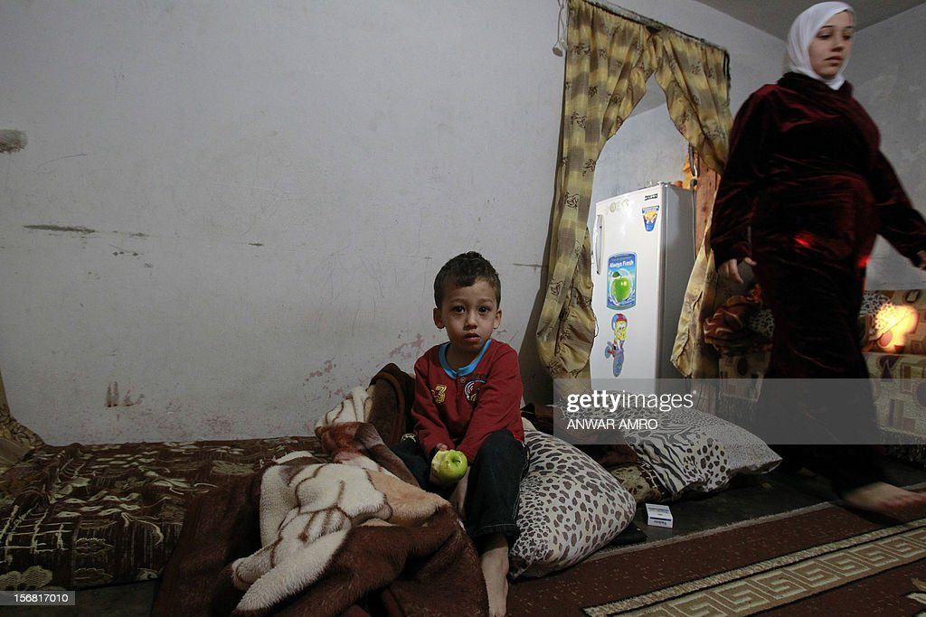 Deeb, a two-year-old Syrian refugee, eats an apple as his mother goes on with her house chores in the northern Lebanese town of Halba on November 20, 2012. Syrian refugees in Lebanon are demanding the creation of a camp like in Turkey and Jordan, but the Lebanese government and the United Nations reject the idea.
