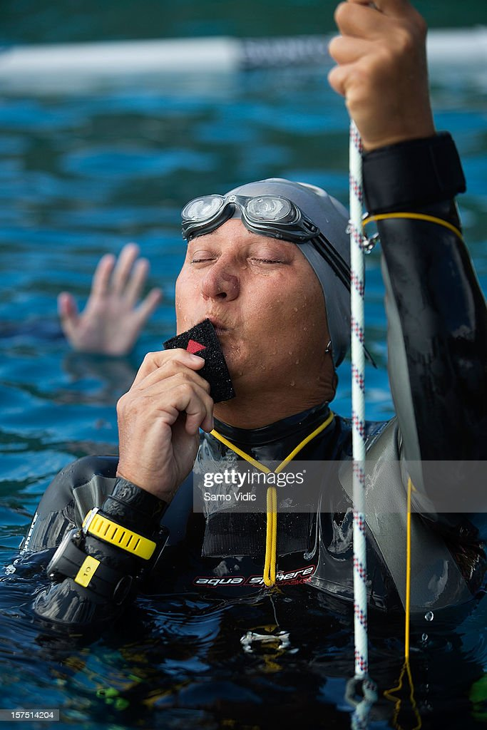 DeeDee Flores of United States kisses the tag after her free dive at the Suunto free diving world cup on November 26, 2012 in Long Island, Bahamas.