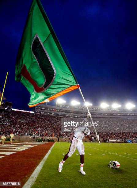 DeeJay Dallas of the Miami Hurricanes waves the flag after they defeated the Florida State Seminoles 2420 during the second half of an NCAA football...