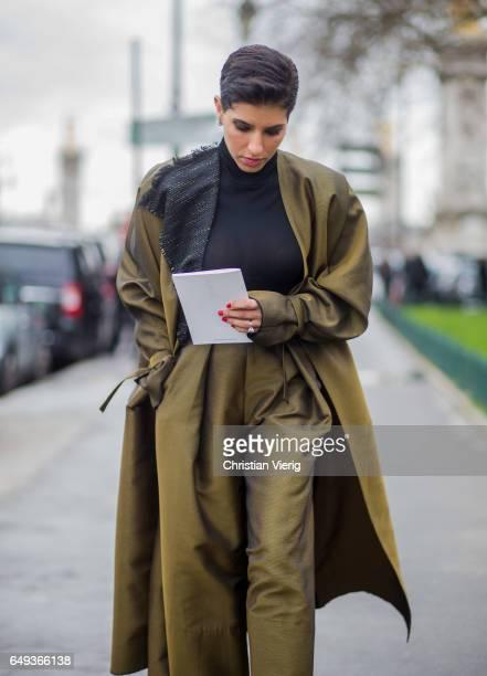 Deena Aljuhani Abdulaziz wearing wide leg pants and coat outside Chanel on March 7 2017 in Paris France