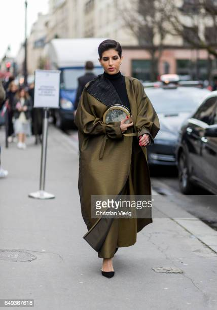 Deena Aljuhani Abdulaziz wearing wide leg pants and coat outside Moncler on March 7 2017 in Paris France
