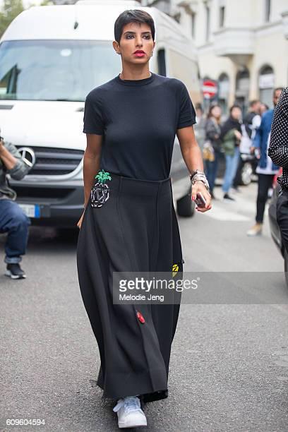 Deena Aljuhani Abdulaziz wears a black top with a black fruitthemed skirt outside the N21 show during Milan Fashion Week Spring/Summer 2017 on...