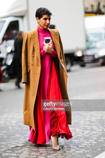 Deena Aljuhani Abdulaziz wears a brown coat a pink and red dress and beige suede boots outside the Undercover show during Paris Fashion Week...