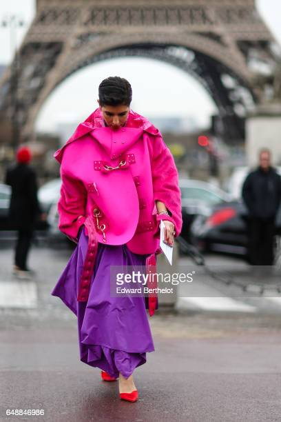 Deena Aljuhani Abdulaziz wears a pink oversized coat with a hood and fur inner lining a purple dress and red shoes outside the Hermes show during...