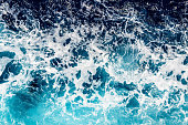 Areal shot of deep blue and rough sea with lot of sea spray