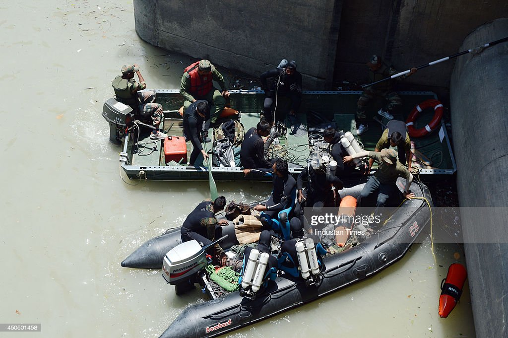 Deep sea divers from navy during the search operations in Beas river tragedy on June 12, 2014 in Mandi, India. Two more bodies were recovered from the river. A wall of water washed away 24 engineering students and a tour operator Sunday evening after water was released into the river allegedly without a warning from a nearby Pandoh Dam on Beas River.