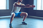 Part of young man in sportswear doing squat at gym