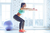 Side view of young beautiful woman in sportswear doing squat and holding dumbbells while standing in front of window at gym